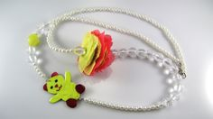 Necklace with pearls and transparent beads, handmade flower made of yellow gauze and coral pink organza and handmade teddy bear made of arzanto, hand painted and coated with liquid glass.