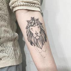 Tatuagem criada por Pétala Cavalcanti de Curitiba.    Leão com flores e linhas ornamentais no braço.