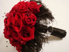 Beautiful red bridal bouquet with a black feather collar and twisted wire bridal bouquet jewelry