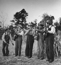 Poor Valley, VA, US- Five male musicians dressed in hats & bib overalls standing in a field playing two guitars, a banjo, fiddle & spoons for percussive accent.- Eric Schaal
