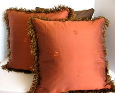 This stunning 18x18 rust colored pillow cover makes an elegant statement in any room. Coordinates with the 18x18 brown faux silk pillows featured in my shop ( see pictures above for coordinated look)  Made from 100% high-end Kashmir designer raw silk with a silk embroidered swirl design  Double lined with flannel interlining and premium cotton sateen lining for a plush look and feel  Trimmed in a dark amber brush trim  Same designer silk fabric front and back  The cover is finished with an…