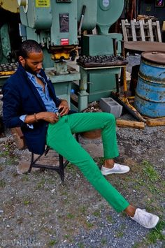 Try pairing a navy blazer with green chinos to achieve a dressy but not too dressy look. Rock a pair of white low top sneakers for a more relaxed aesthetic.   Shop this look on Lookastic: https://lookastic.com/men/looks/blazer-denim-shirt-chinos-low-top-sneakers-bracelet/13238   — Blue Denim Shirt  — Navy Blazer  — Brown Bracelet  — Green Chinos  — White Low Top Sneakers
