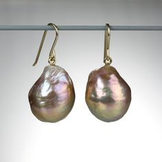 A pair of 18k yellow gold, high luster, metalic pink freshwater baroque pearls. Pearls measure approximately 15mm x 19 mm.
