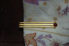 (Swank?) Red stone tie bar.  Soft golden triple bar, with a red glass stone in the center. Tres chic! Very deco look! Beautiful vintage men's jewelry.    Tie bar is part of my personal collection, and is currently for sale.