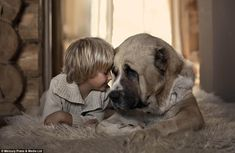 A young boy rests his head against his loyal companion as they snuggle up together on a cosy rug