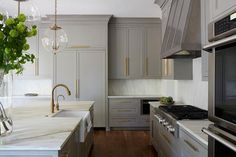 Gold and gray kitchen features creamy gray cabinets adorned with long brushed brass pulls paired with white marble countertops and backsplash. A dark metal kitchen hood with rivets stands over a stainless steel stove placed next to enclosed double ovens. A pair of Regina Andrews Large Globe Pendants illuminate a gray kitchen island with legs fitted with a sink and brushed brass gooseneck faucet.