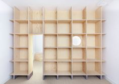 Bedroom door through shelving - like this, only modules to be more designed.... Aurélie Monet Kasisi adds wooden walls to family home