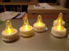 clear baby bottle nipples over electric flame tea lights, such a cute baby shower idea by MarylinJ