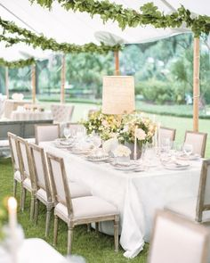 Wooden lamps with raw-burlap shades illuminated centerpieces of greige cement pots filled with dahlias, hydrangeas, and ranunculus.