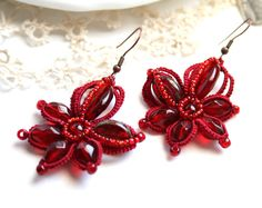 A deep red color cotton thread tats a flower style earring for your wearing enjoyment. Four red glass beads for the petals of the flower with a large flat oval and a oval Czech glass beads for the other two petals. A round glass bead for the center outlined with red seed beads  Tatting is a long ago technique for creating lace. I have taken this process to another level in this beautiful pair!  Earrings measure 2 inches in length and 1 1/2 in width. I measure the length of the earring fr...