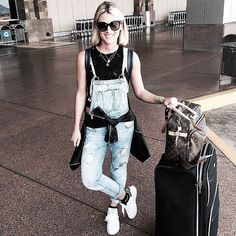 Denim overalls paired with sneakers.