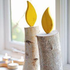 Raccogli insieme ai bambini pezzi di tronco (meglio se di betulla). Poi aiutali a realizzare la fiammella in compensato (ma va bene anche in cartoncino) e ad assemblarla col tronco per costruire delle