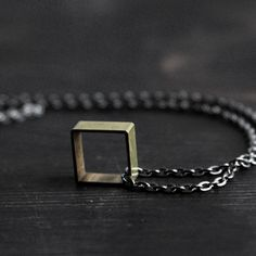 This cube pendant hangs freely from an 18-inch gunmetal iron chain with a lobster clasp. Crafted from raw brass, the pendant features the subtle lines and gradations of natural oxidation.