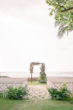 """From the editorial """"Think Tropical Can't Be Timeless? Allow This Hawaiian Wedding Weekend to Prove You Wrong."""" This ceremony took place in a garden lawn on Lanikuhonua Beach in front of a stunning ocean view and the arch was arranged to perfection by @passionroots. We're sharing all the details on SMP! Photography: @kerryjeannephoto #hawaiiceremony #tropicalceremony #destinationceremony #ceremonyinspiration"""