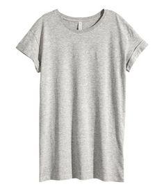 Zwart. Een lange top van tricot met korte mouwen met een vastgestikte omslag onderaan.