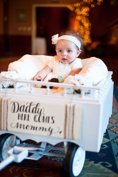 "Cute flower girl in ""Daddy, here comes mommy"" wagon at Church Landing Wedding in Meredith, NH"