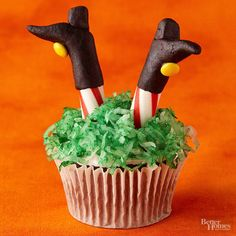 This coconut-topped Halloweenwitchcupcake may look more than a little wicked, but we promise it will be sweet. To make the Halloween dessert recipe, follow these cupcake decorating steps: 1. Mold black marzipan boots around two peppermint sticks to create the legs. 2. Stick yellow mini candy-coated chocolates on each boot for the buckles, using frosting to secure. 3. Dye coconut green with food coloring; top a frosted cupcake with the coconut. 4. Insert peppermint sticks into the cupcake./