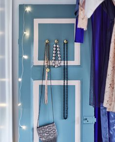 An old wooden door is painted light blue and white, with knobs added to hang jewelry.