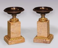 A small pair of early 19th Century bronze, ormolu and marble Tazzas, having reeded rims and leaf decorated stems, raised on sienna marble square plinth bases. Circa: 1825 Ref: 5637