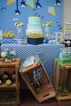 Caixotes de feira foram usados na decoração dessa mesa do bolo de aniversário de um ano com o tema brinquedos de menino. A mesa também contou com um baleiro. As cores escolhidas foram azul, amarelo e verde.