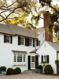 Traditional home with white shake exterior, black shutters and trim shrubbery (by Steven Gambrel)