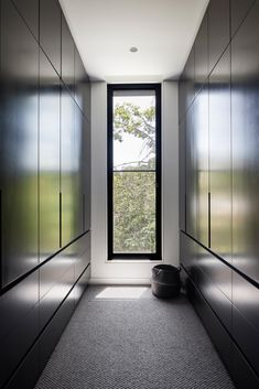 In this modern walk-in closet, theres dark floor-to-ceiling cabinetry that lines the walls, and allows the eye to focus on the tree view through the window.