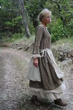 The apron appears to be tied on the side. If it is tied on both sides, so the sides are open,that's a really cool look.  We can recreate this by cutting up a skirt.