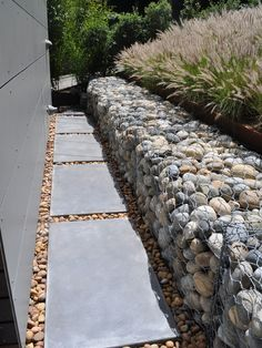 Nice way to soften an edge.  Gradual change of material and heights.  Something like this could help to break  down the big driveway wall    Google Image Result for http://st.houzz.com/simages/1286081_0_15-2861-modern-landscape.jpg