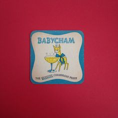 """Sweet little coaster showing the Babycham deer underneath the words """"I'd Love A Babycham"""". In reasonable condition overall with some age-related wear to corners (pictured) and approximately 9cm squared, fairly standard coaster size.All items are authentic vintage goods, specially selected for robertafidora.com and as such, items may show signs of wear consistent with age and use."""