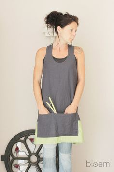 Here is a hand made linen apron in a gorgeous color combination of slate grey with fresh Spring green.  When I made a sac à pain in this color combination, I loved it so much that I wanted to make an apron in the same colors. Voilà, here the result.  Easily put on, meaning, hopla over the head, no buttons, no bands to wrap around the waist, and it falls into place, loose fit and open on the back for easy sitting and bending over when working.    The aprons are available in sizes XS-S size…