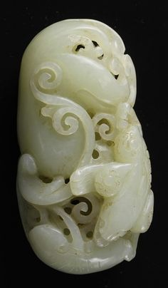 China, 19th C., carved jade ornament featuring a diving fish and swirling botanical forms. Length 3 1/4 in., Width 1 3/4 in.