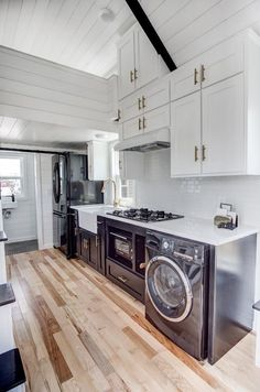 The kitchen is finished with black and white cabinets, black stainless steel appliances, white quartz countertop, and tile backsplash.