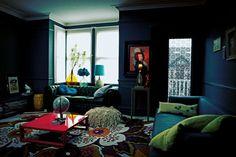 peinture salon moderne bleu marine, canapé Chesterfield en cuir noir et canapé tapissé noir avec coussins verts