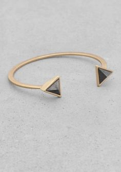 An edgy cuff featuring pyramid-shaped stone details.