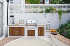 Backyard Landscaping Ideas – This small patio space is ready for a party with its built-in BBQ and plenty of seating - This modern landscaped garden has a bespoke outdoor kitchen with a bbq, counter space and storage. Small Patio Spaces, Small Outdoor Kitchens, Small Patio Design, Modern Outdoor Kitchen, Outdoor Kitchen Cabinets, Outdoor Living, Outdoor Decor, Outdoor Benches, Kitchen Island