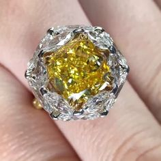 A masterpiece setting with a 4+ carats Cushion Shape Fancy Vivid Yellow diamond ring surrounded by oval and marquise shape diamonds. Stunning and creative.