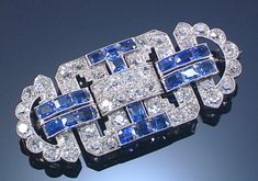 SAPPHIRE AND DIAMOND BROOCH, 1930S. The open work plaque of geometric design millegrain-set with circular-cut diamonds and cushion-shaped sapphires.