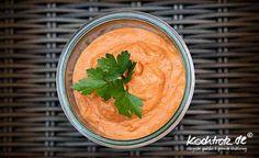 Paprika-Hummus - Das Rezept ergibt circa 500 ml.  - Kichererbsen aus dem Glas (oder getrocknete, dann 150 g), rote Paprika (3 frische oder 1 Glas geröstete Paprika), Knoblauchzehen, Zitronensaft, Olivenöl, Tahini Sesampaste, Salz, Pfeffer, Chayennepfeffer, Kreuzkümmel, Bei der schnellen Version einfach alle Zutaten