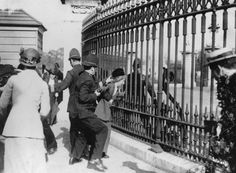 A police officer tries to remove a suffragette from the railings outside Buckingham Palace