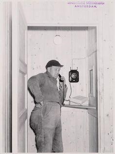 1956 Dit is een van de mannen die de eerste huizen van Slotervaart heeft gebouwd. Hij staat te bellen met de eerste telefoon van Slotervaart. Het toestel hing aan de muur in de eerste bouwkeet, die in 1955 in gebruik werd genomen. De keet stond waar nu de Jacob Geelstraat is en was voor die tijd heel groot en modern. Je kon er niet alleen telefoneren, de bouwvakkers konden zich er ook wassen na het werk. Er was een kantine bij en twee vriendelijke dames zorgden voor de koffie.