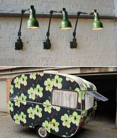 Love the trio of industrial wall mounted lamps.  (Not so much the floral caravan.)   Via 13zor (in French)