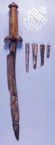"""65 ballock daggers were found on the Mary Rose. Although the blades are usually lost to corrosion, all but one appears to have had a single-edged blade. The handles are mostly made of Boxwood, although other woods used include Ash, Maple and either Hawthorn or Rowan.    The example illustrated is still sheathed, and was found with several small """"by-knives"""", stored in small pockets on the outside of the main sheath. This was not uncommon in those found on the Mary Rose.    Image ©Mary Rose…"""