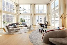 Decorator Amy Lau used oversize, theatrical pieces by Vladimir Kagan and Lindsey Adelman to complement the 19-foot ceilinged and glass-walled living room of this downtown Manhattan triplex.