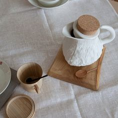 textured, white porcelain and smooth, wooden coffee cups