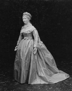 1870 Three-piece Wedding dress. Pale gray-blue taffeta wedding dress. Bodice buttoned down front, fitted, long bell shaped sleeves, trimmed at neck, around yoke, and around lower edge of sleeves with fringed pleated whited taffeta ruching and machine made lace. Skirt plain in front, fastened with placket left front, longer in back to form train, very full in back. Belt with peplum-like bow in center back.| Museum of Fine Arts, Boston