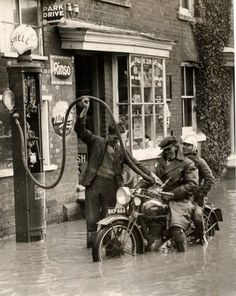 Shell. England 1935. A gas station attendant fills the tank on a motorcycle carrying two people during a small flood. Everyone seems so chipper.