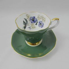 Green tea cup and saucer made by Royal Grafton. Flowers on the inside rim of the tea cup and in center of the saucer. Gold trimming on cup and saucer edges. Excellent condition (see photos). Markings read: Royal Grafton Fine Bone China Made in England Please bear in mind that these