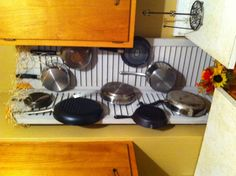Pots and pans storage for limited cabinet space, utilizing an unusable corner.