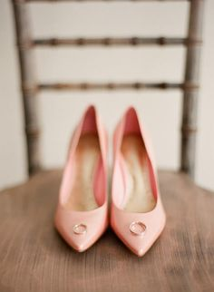 A bride's blush heels provide a bright backdrop for the couple's wedding rings. #weddings