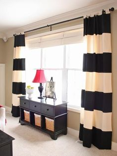"Simple, but so sophisticated, black-and-white striped drapes create an instant focal point of an oversized window — and don't have to cost a fortune, says designer Sarah Macklem of The Yellow Cape Cod, who made the window treatments herself. ""I used iron-on fabric bonding tape to attach black fabric stripes to ready-made twill drapes, finishing the raw edge with grosgrain ribbon. This was a simple and inexpensive DIY project that had huge impact in the space. These drapes are a great…"